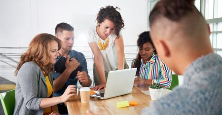 Groupe de jeunes employés occasionnels discutant d'un projet de remue-méninges tout en recherchant des idées sur un ordinateur.