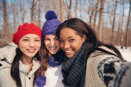 Groep van duizendjarige jonge vrouwelijke volwassen vrienden genieten van de winter en in een sneeuw gevulde park