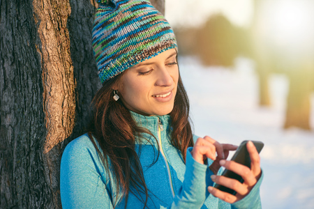 mobile sms: Serene lady texting on a smartphone after a winter workout