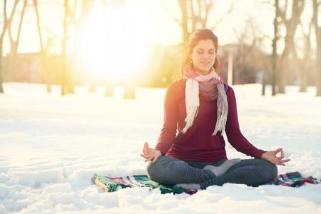 winter sunrise: Serene lady relaxing and meditating doing yoga poses
