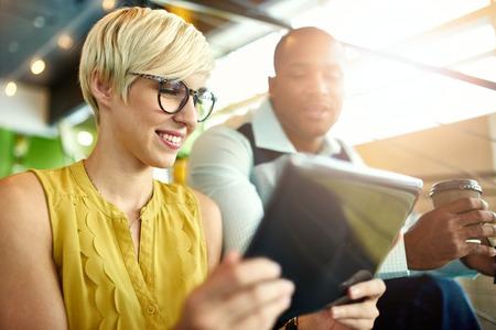 Équipe de jeunes gens d'affaires occasionnels collaborant à un projet en ligne à l'aide d'une tablette tactile numérique dans un espace de bureau moderne et lumineux. Série avec des fusées éclairantes Banque d'images