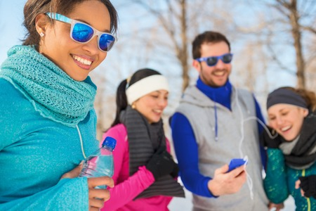Group of millenial young adult friends enjoying music from a phone on headphones in a snow filled park