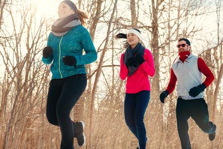 Groep van duizendjarige jonge volwassen vrienden training voor cross-country lopen in de winter in een sneeuw gevulde park