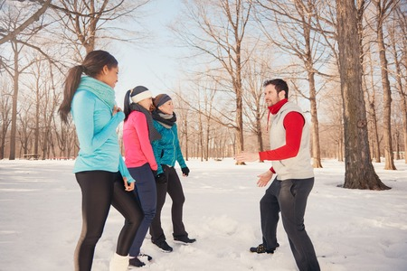strengthen: Group of millenial young adult friends stretch and strengthen in a snow filled park