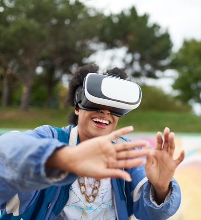 Smiley young African American woman alienated by new technology wearing VR goggles in a skate park outside Stock Photo