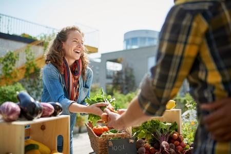 Vriendelijke vrouw neigt een biologische plantaardige kraam op een boerenmarkt en verkoop van verse groenten uit de tuin op het dak