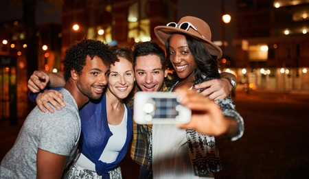 屋上テラス、夜間ストロボを使用しての携帯電話で selfie 写真を撮る友人の多民族 millenial グループ