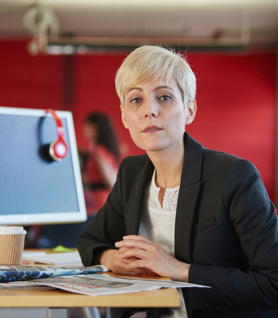 Confident female designer working in red creative office space