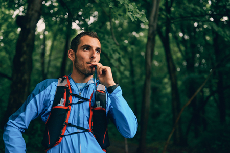 Fit male jogger hydrates while day training for cross country forest trail race in a nature park.