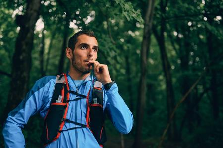 フィット男性ジョガー国林道クロス トレーニングのための自然公園でレース中の水和物します。
