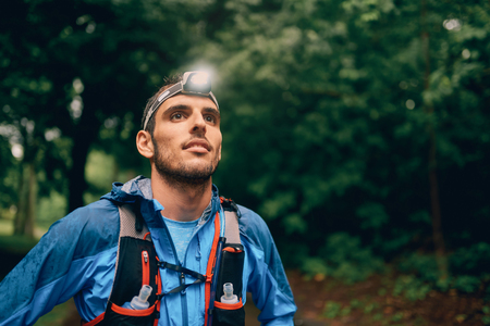 Fit male jogger with a headlamp rests during training for cross country trail race in nature park. Stock Photo