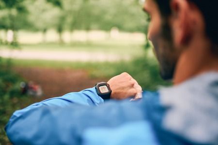 Fit male jogger day using a smartwatch during cross country forest trail race in a nature park. 版權商用圖片