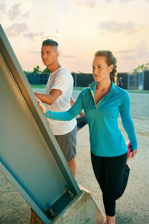 Male and female athletes stretching before going jogging outdoors Stock Photo