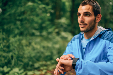 Fit male jogger day using a smartwatch during cross country forest trail race in a nature park. Stock Photo