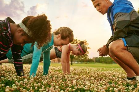 자연 공원에서 석양을 팔 굽혀 펴기를하는 피트니스 훈련 중 여성의 다양한 그룹