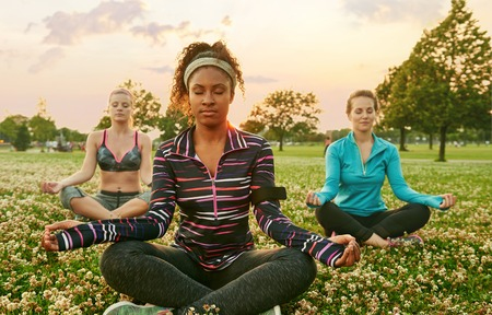 Young african-american woman leading a yoga class at sunset in nature park