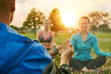 Yoga class of diverse millennials on the grass at sunset in nature park