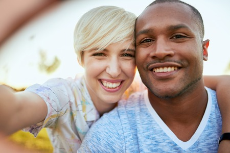 Mixed race couple of millennial in a grass field taking a selfie with a smartphone Stock Photo