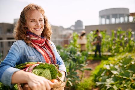 Vriendelijke vrouw het oogsten van verse groenten uit de kas op het dak tuin
