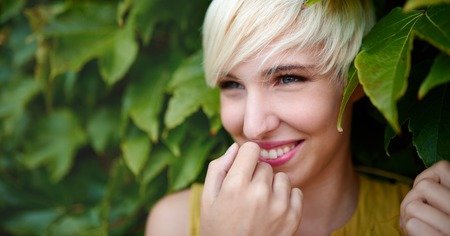 Beautiful short haired platinum blond woman standing against an ivy fence backdrop Stock Photo