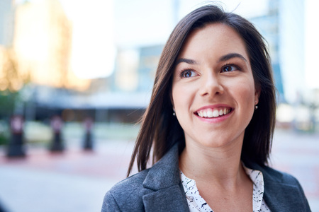 telecommuter: Millenial businesswoman smiling confidently with cityscape background
