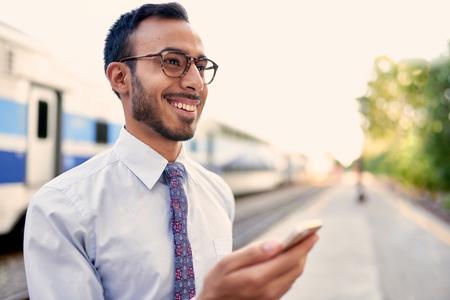 telecommuter: Confident Indian businessman checking his smart phone on a train platform