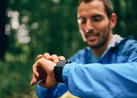 Fit male jogger day using a smartwatch during cross country forest trail race in a nature park. Imagens