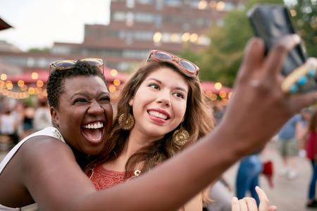 Diverse groep van twee meisjes nemen selfies foto's in de menigte van een festival zomerfestival Stockfoto