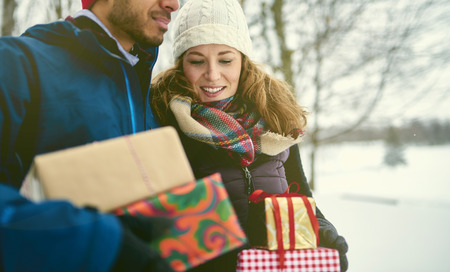Smiling diverse couple holding Christmas presents while walking through a winter forest Stock Photo