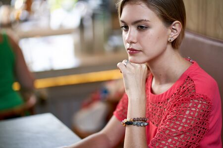 Closeup lifestyle portrait of young pensive blonde caucasian millennial woman sitting in a bright modern restaurant wearing bright clothing Foto de archivo