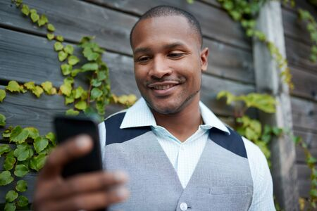 Handsome black man hanging out and texting with his mobile smartphone outside next to a wooden fence