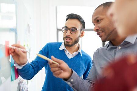 Retrato de un hombre indio en un equipo diverso de compañeros de trabajo millennials creativos en una puesta en marcha de estrategias de lluvia de ideas