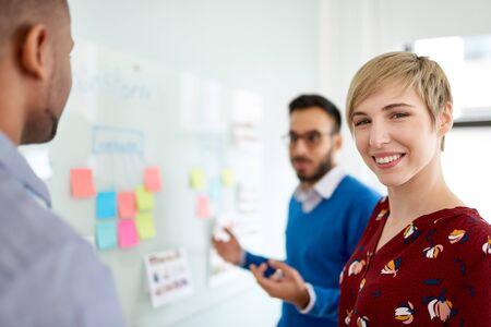 Ritratto di una donna bionda sorridente con i capelli corti in un team diversificato di collaboratori creativi millenari in strategie di brainstorming di avvio Archivio Fotografico