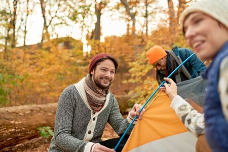 Group of Canadian hikers setting up a tent in a fall forrest