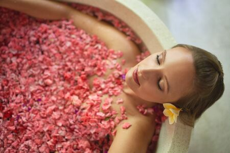 Overhead shot of natural millennial woman in luxurious spa bathtub filled with flower petals in tropical resort and wellness centre