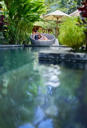 Candid shot of young caucasian couple lounging in modern chair near luxurious pool of tropical hotel and spa in Bali 版權商用圖片 - 128242803