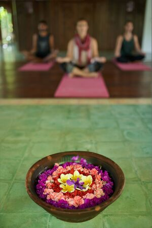Close up of flower offering for prayer in traditional Indonesian temple in Bali with three diverse people meditating in background 版權商用圖片