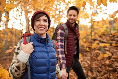 Attractive caucasian couple hiking through the forest in the fall in Canada