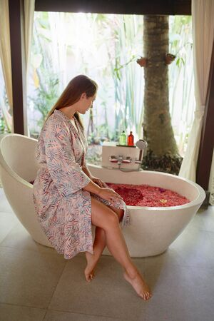 Beautiful millennial woman being pampered at tropical resort and spa with serene herbal bath and flower therapy in Bali