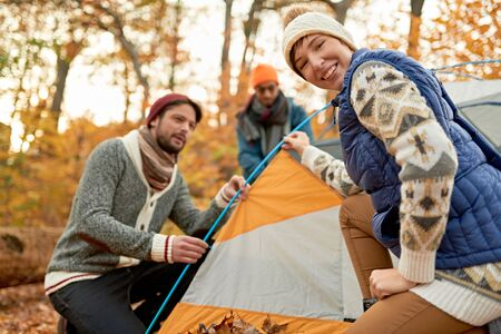 Group of Canadian hikers setting up a tent in a fall forrest 版權商用圖片 - 128242843