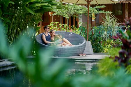 Candid shot of young caucasian couple lounging in modern chair near luxurious pool of tropical hotel and spa in Bali 版權商用圖片 - 128242852