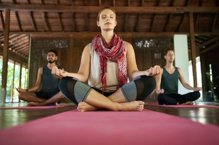 Mindful woman teaching meditation to two multi-ethnic men in lotus pose on yoga mats in traditional temple in Bali Indonesia
