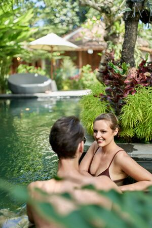 Unposed shot of romantic couple relaxing together in lush resort pool of luxurious hotel in tropical Bali during retreat 版權商用圖片