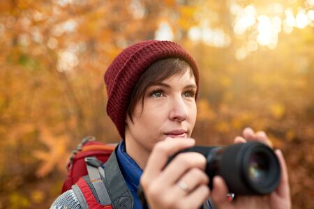 Attractive caucasian girl taking pictures with a mirrorless camera through the forest in the fall in Canada 版權商用圖片 - 128242854