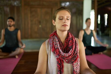 Woman giving meditation course to two multi-ethnic men on yoga mats in traditional temple in Bali Indonesia 版權商用圖片