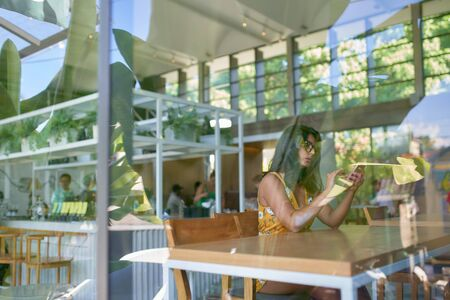 Lifestyle shot of fashionable hispanic millennial influencer typing on cellphone in modern trendy and bright coffee shop with plants