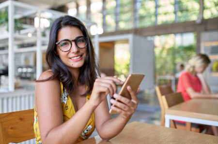 Candid lifestyle portrait of laughing hispanic millennial model typing on cellphone in modern trendy and bright cafe with plants