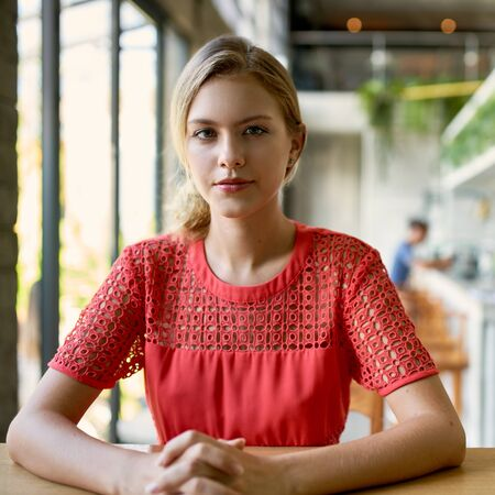 Lifestyle portrait of confident young trendy millennial woman with blonde hair sitting at wooden table in bright and modern restaurant 版權商用圖片 - 128243008