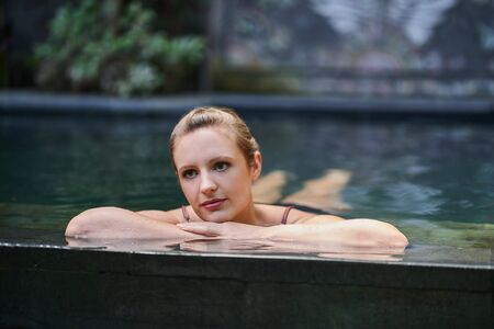 Beautiful woman relaxing outdoors in lush and exotic stone swimming pool of luxurious resort during tropical holiday in Bali