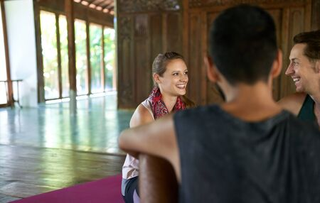 Candid shot of beautiful female meditation teacher discussing with mixed-race male students about yoga course and Indonesian culture in Bali 版權商用圖片